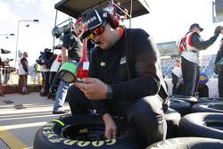 Hscott Motorsports mechanic checks tire pressures
