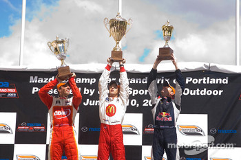 Sébastien Bourdais tries to lift his trophy above the others
