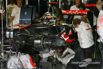 Mechanics and Engineers work on the car of Fernando Alonso, McLaren Mercedes, MP4-22 during the session