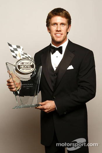 Carl Edwards holds the trophy given to the ninth place driver in the NASCAR NEXTEL Cup Series standings