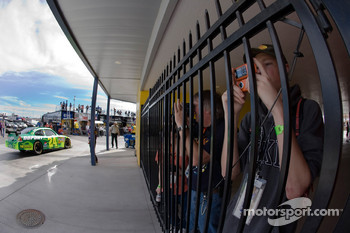 Fans try to photograph their favorite drivers as they walk by in the garage area