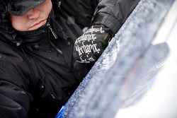 A crew member works on the teams car as snow falls at Atlanta Motor Speedway