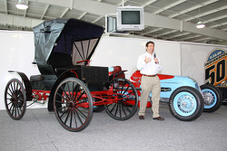IMS President and COO Joie Chitwood stands between a 1905 Sears and Roebuck catalog kit car, left, and the car that his grandfather, Joie Chitwood, drove to fifth in the 1946 Indianapolis 500