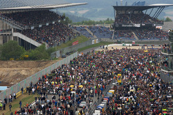 A large crowd on pitlane and track before the race