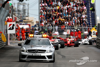 The safety car leads the field