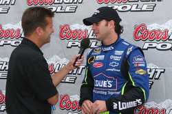 Jimmie Johnson talks to the public address system after winning the pole
