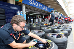 A Scuderia Toro Rosso crew member with tyres in front of the garage