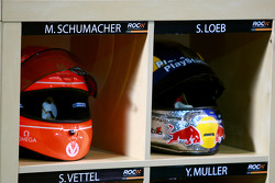 The helmets of Michael Schumacher and Sébastien Loeb in the pits