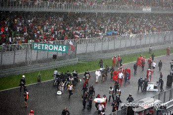 Mechanics on the track, after the race was red flagged due to rain