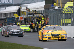 Marcos Ambrose leads the field out to the track after a race interruption to put rain tires