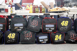 Bags with drivers names and car numbers sit underneath a team's lunch station in the garage area