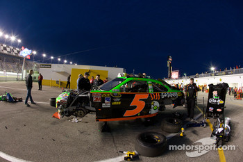 Hendrick Motorsports Chevrolet crew members work on the wrecked car of Mark Martin