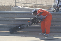 A marshall clears the front wing of Karun Chandhok, Hispania Racing F1 Team from the track