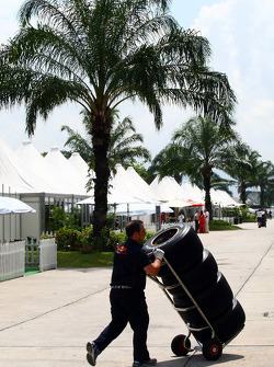 Toro Rosso Mechanic in the paddock pushing tyres