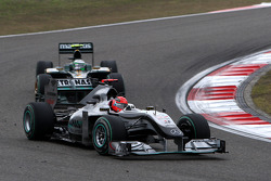 Michael Schumacher, Mercedes GP leads Heikki Kovalainen, Lotus F1 Team