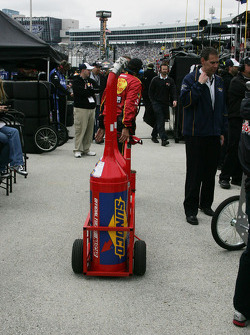 Crew member for Jamie McMurray totes gas cans back to the gas pumps