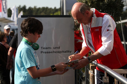 Dr Ullrich, motorsport director Audi signs autographs in the paddock