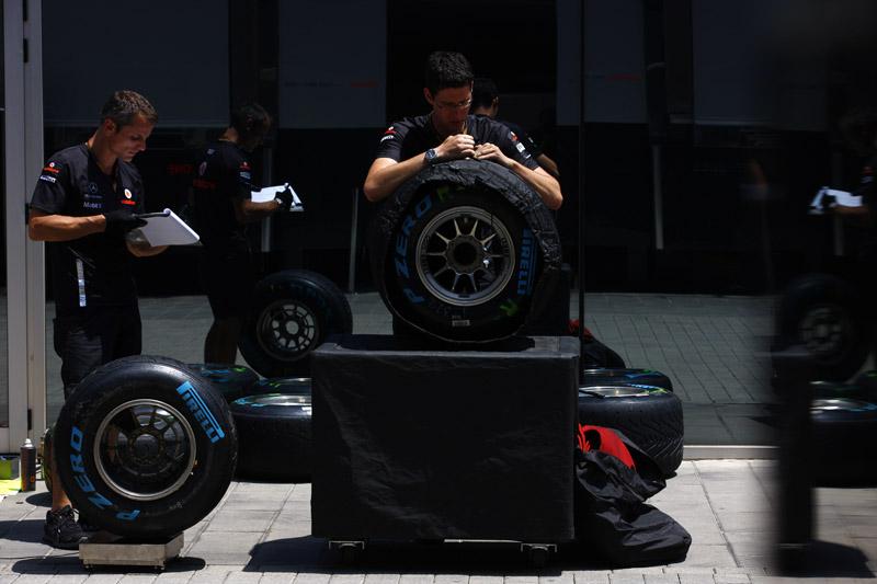 Mecânicos da McLaren trabalham com pneu em Valência