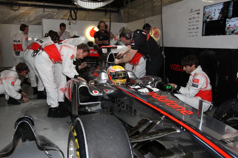Hamilton observa os mecânicos trabalhando em seu carro antes do GP da China