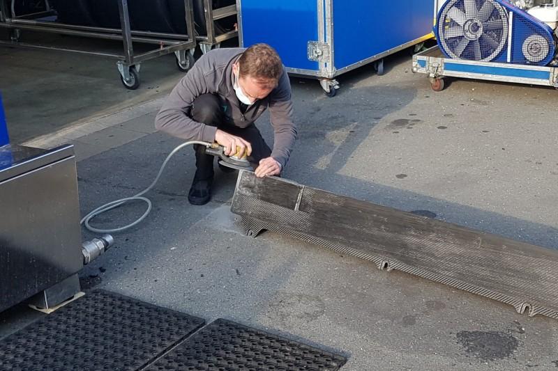 Mechaniker schleift Carbonschürze