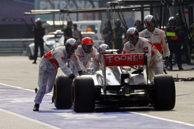 Mechaniker schieben den McLaren von Jenson Button zurück nach einem fehlerhaften Boxenstopp beim Formel-1-Rennen in China 2013