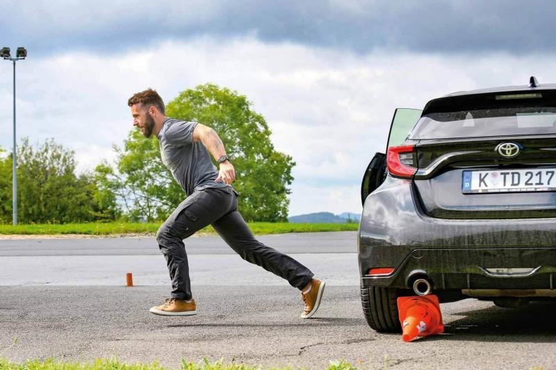Ein Mann sprintet nach links von einem schwarzen Toyota Yaris weg, der von hinten zu sehen ist.
