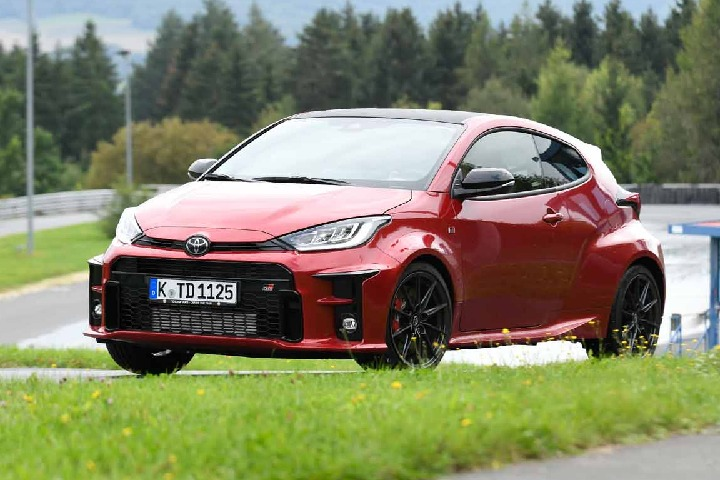 Ein roter Toyota Yaris ist von vorne seitlich zu sehen, wie er auf einer Rennstrecke fährt; im Vordergrund ist ein Grünstreifen, im Hintergrund ist Wald zu sehen.