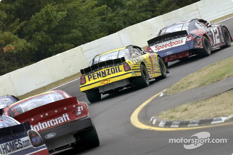 Jeremy Mayfield behind the wheel leads a pack of cars through a turn at The Glen