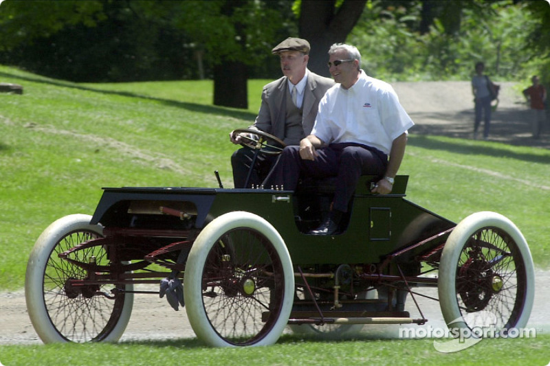 Glenn Miller, development engineer at Ford Special Vehicle Engineering, and Dale Jarrett (1999 NASCAR Winston Cup Champion) cruise around the activities field in a newly replicated Ford 1901 Sweepstakes restored vehicle