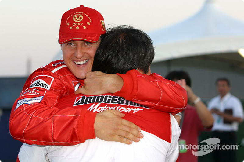 Michael Schumacher celebrates with a Bridgestone team member