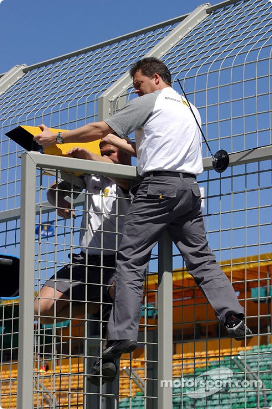 Renault crew members prepare pit wall area