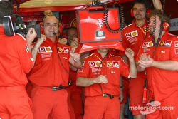 Ferrari team members celebrate Rubens Barrichello fastest time