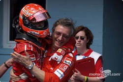 Race winner Michael Schumacher celebrates with Paolo Martinelli