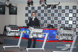 Joe Negri stands next to three generations of IndyCarTM engines