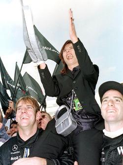 Mika Hakkinen's wife Erja is lifted up by the McLaren mechanics