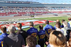 Pit crews line pit road as drivers complete a five lap tribute to Dan Wheldon