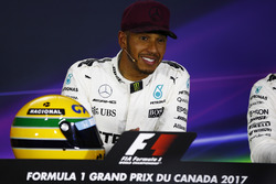 Lewis Hamilton, Mercedes AMG F1, shows off his Ayrton Senna helmet, a gift after equalling the Brazilian's pole record, in the post-qualifying press conference
