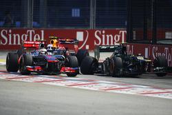Lewis Hamilton, McLaren y Mark Webber, Red Bull Racing pasean el Caterham chocado de Vitaly Petrov, Caterham