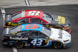 Clint Bowyer, Michael Waltrip Racing Toyota and Aric Almirola, Richard Petty Motorsports Ford battle on pit road