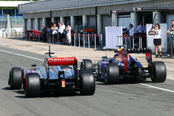 Sebastian Vettel, Red Bull Racing RB9 passes Gary Paffett, McLaren  MP4-28 Test Driver in the pit lane