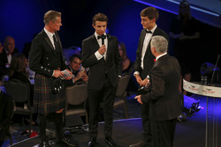 Derek Warwick receives an award from Lando Norris and George Russell