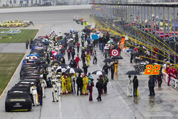 The cars are parked on pitlane after the rain starts