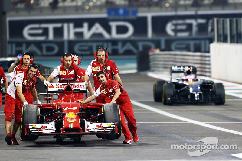 La F14-T Ferrari di Fernando Alonso, Ferrari, è riportata di nuovo ai box nella seconda sessione di prove libere dai meccanici mentre passa Jenson Button, McLaren MP4-29