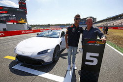 Daniel Ricciardo, Red Bull Racing, and Martin Brundle pose with a Pirelli Hot laps Aston Martin DB11