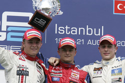 Podium: race winner Heikki Kovalainen with Adam Carroll and Nico Rosberg