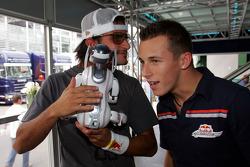 Vitantonio Liuzzi and Christian Klien play with a Sony Aibo robot dog