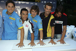 The F1 Drivers make hand prints on a sheet to be auctioned
