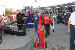 Crew members tow gas can through the maze of the pit lane