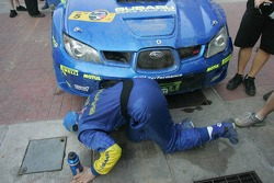 Petter Solberg inspects his car