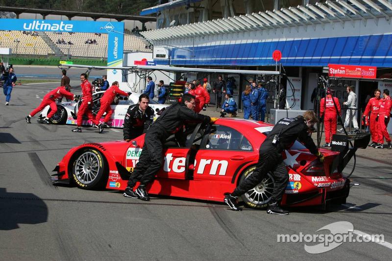 Mécaniciens dans la voie des stands poussent la voiture de Jean Alesi et Stefan Mücke